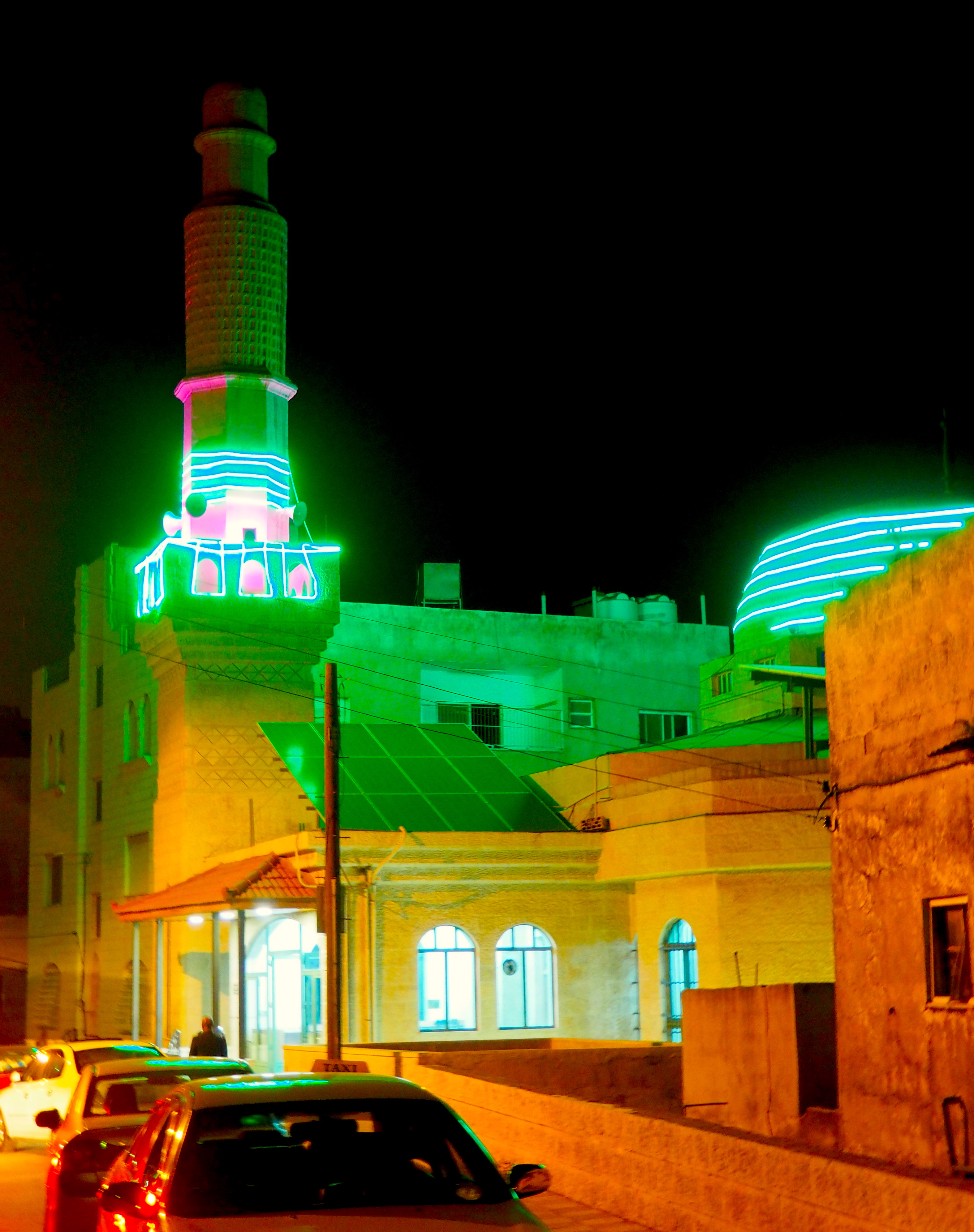 The green glowing lights of a mosque in Amman, Jordan